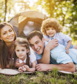 Young parents with their little children enjoying in family camping.  [url=http://www.istockphoto.com/search/lightbox/9786778][img]http://dl.dropbox.com/u/40117171/family.jpg[/img][/url]